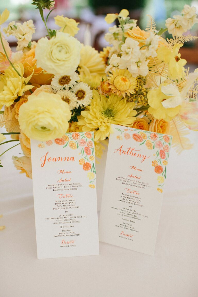 Yellow centerpiece styled with watercolor wedding programs