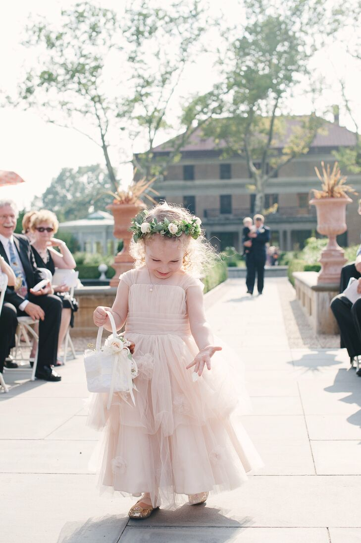 Tara's niece was the flower girl and wore a peach tulle dress with a floral wreath in her hair. She carried rose petals down the aisle in a basket that was decorated with garden roses and light peach ribbons that matched her dress.