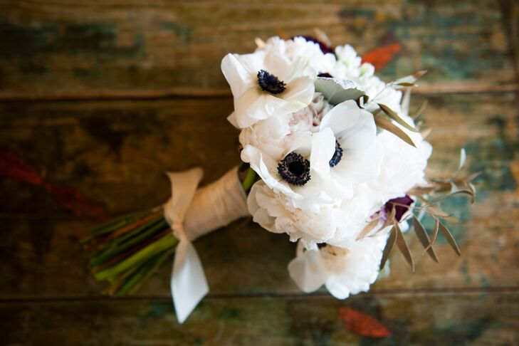Kristen carried white anemones, blush peonies and olive leaves in her lush white bouquet.