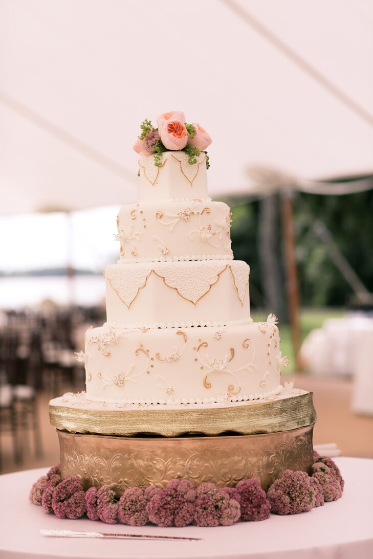 The four-tiered ivory wedding cake was placed on top a gold metal cake stand and was decorated with gold accents. On the top of the cake was a small arrangement of pink roses.