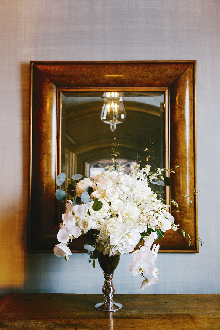 Silver vases held large, lush arrangements of white roses, peonies and orchids.