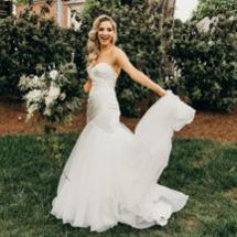 bride in wedding dress holding train