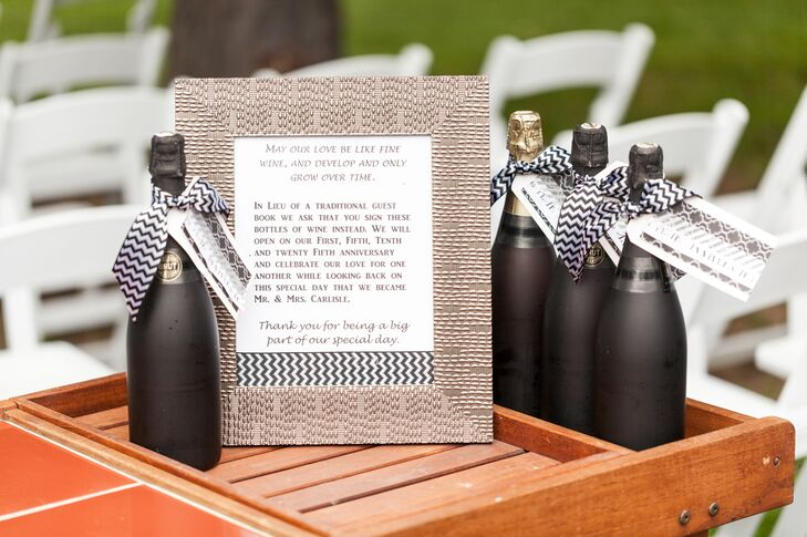 Black-painted wine bottles had black-and-white-striped ribbon wrapped around the neck. Guests signed the bottles as an alternative to a guest book.