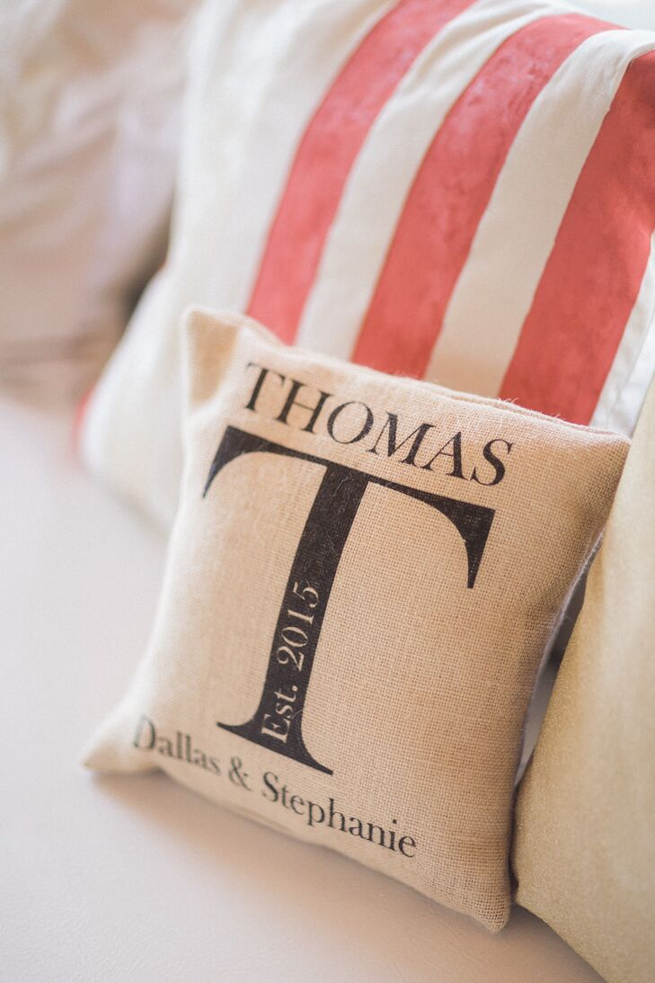 "To make their indoor space more personalized, Stephanie and Dallas also had a few custom pieces. Aside from an embroidered ""Mr. & Mrs."" accent, they had a neutral pillow with their name, wedding year and new last name printed on the front."