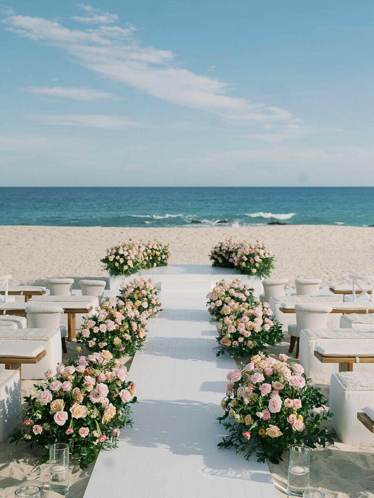 Beach ceremony aisle with rose floral arrangement decorations