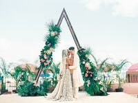 Couple hugging in front of triangle arch with tropical leaf decorations