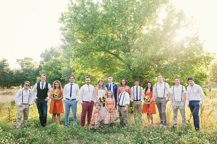 Nicole didn't choose a wedding color, yet her bridesmaids all wore orange silk dresses and the groomsmen wore suit pants held up with suspenders that matched the rustic and outdoor setting.