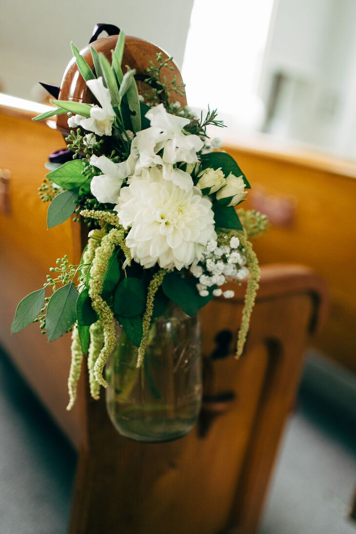 A mason jar filled with white sweet peas, roses, a large dahlia and assorted greens were hung on the sides of the pews for the romantic, rustic ceremony decor.