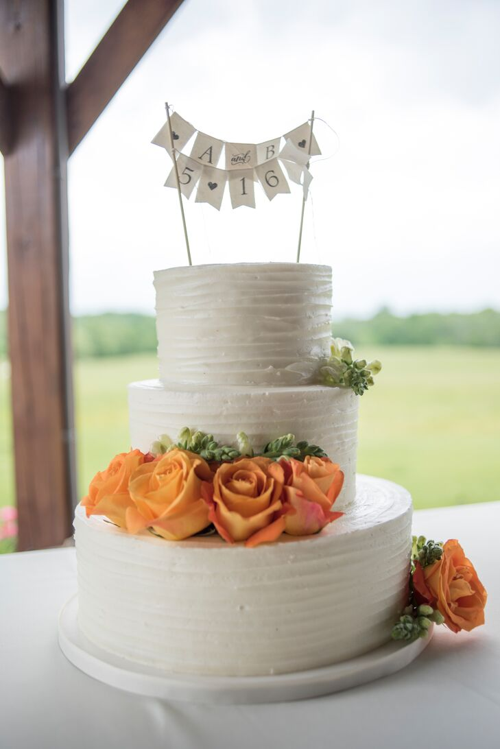 This three-tier buttercream wedding cake had orange roses, inspired by the colors of the University of Tennessee. A cake topper of pennant flags with Andrea and Byron's initials and wedding date added a shabby-chic touch.