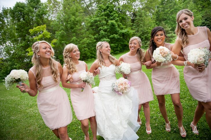 Amber's bridesmaids donned short blush bridesmaid dresses with cream-colored sashes.