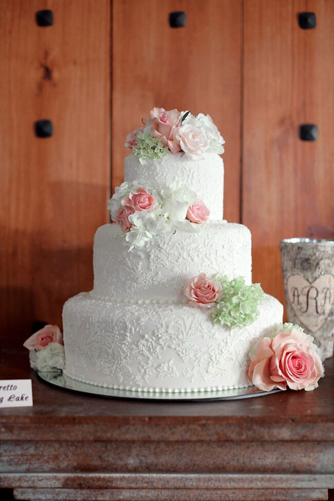 Anna and Adler's three-tier white cake had intricate floral fondant details and fresh cake flowers in white, blush and green. In addition, the cake table had five other cake flavors, so everyone could pick their favorite.
