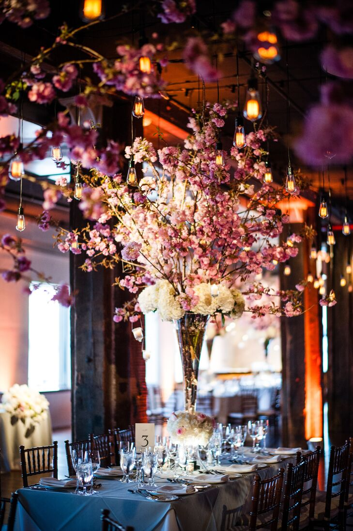 While the cherry blossom centerpieces were an essential component in bring the couple's vision to life, strands of Edison bulbs carefully positioned throughout the room by Pegasus lighting were key in infusing the room with warmth and ambiance.