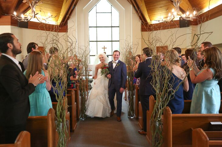 """Stacey and Eric exchanged vows at The Chapel At Beaver Creek in Avon, Colorado. They decorated the space with tall curly willow branches placed every three rows. """"It created a trail through a forest to the front,"""" Stacey says. """"The church itself had beautiful views because it sat right next to the gore creek and had bronze antler chandeliers hanging from the ceiling. There was not a lot we needed to do to because it was beautiful all on its own."""""""