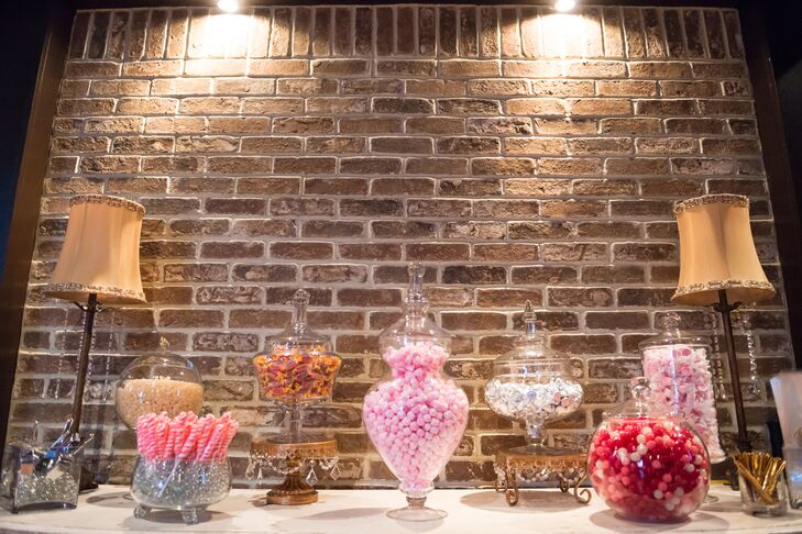 Jillian and Evan had a candy bar at their reception. The sweets were displayed in glass vases and jars on antique-style stands.