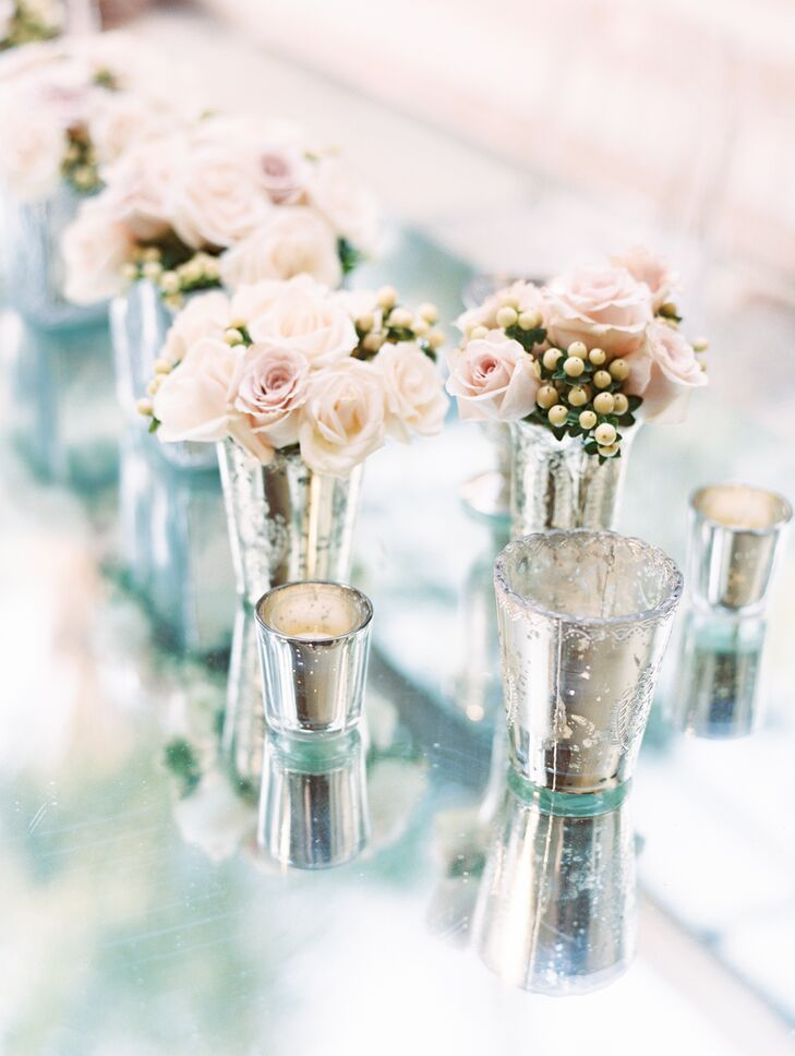 At the reception, clear glass tables were topped with chic textured silver vases filled with pink roses.