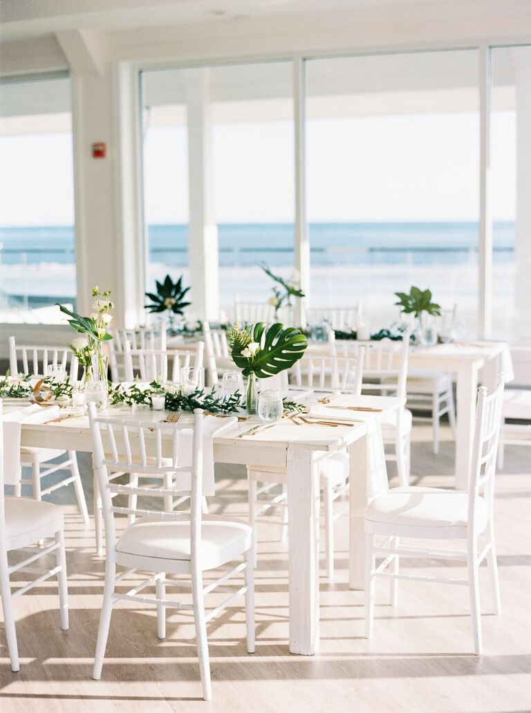 All-white reception decor with tropical leaf centerpieces