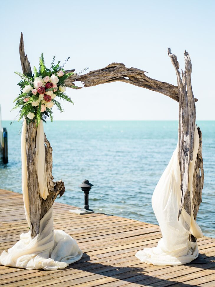 """""""I knew I wanted the driftwood arch. I had seen every blog on every Florida Keys wedding going back five years, and I just had to have that arch,"""" Nicole says. For the rest of her ceremony decor, she borrowed lanterns from her neighbor, filled them with candles and white rose petals. """"Other than that, we let the arch and ocean speak for themselves."""""""