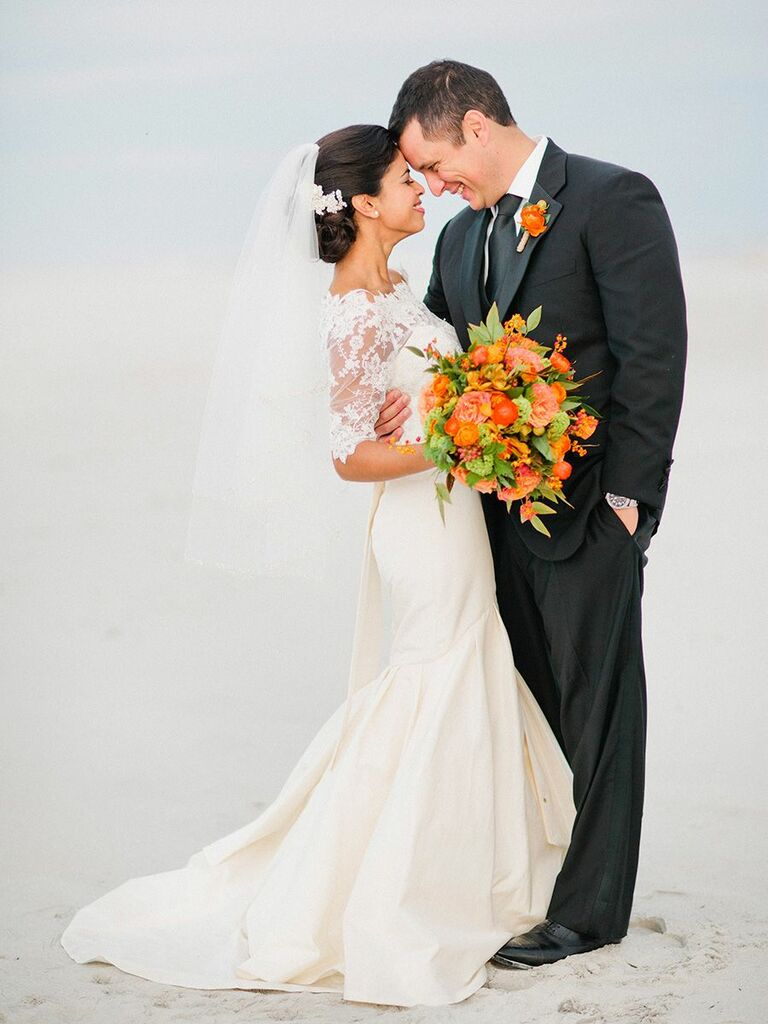 bride and groom on the beach with orange flowers