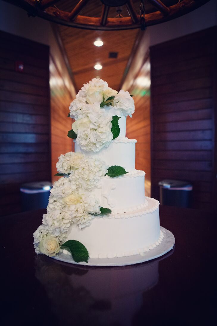 B&G Catering designed the couple's four-tier white wedding cake with a simple, elegant cascade of white hydrangeas.