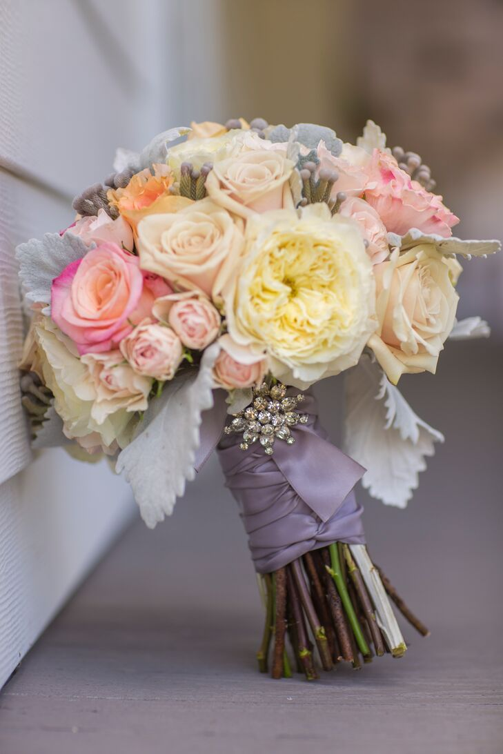 Beth's bouquet consisted of peach and pink roses, white ranunculus flowers and dusty miller. The bouquet was wrapped in purple ribbon and held together with a rhinestone brooch.