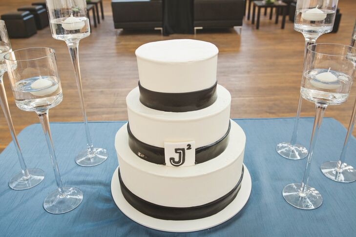 """The three-tiered wedding cake was dominantly white with black at the bottom of each tier. A """"J"""" with a two in the corner represented that both grooms' names were Jason."""