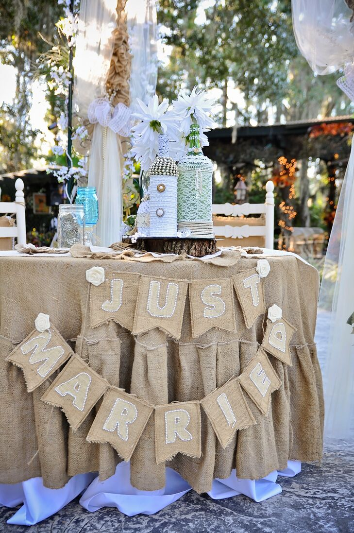 """Their sweetheart table was covered in burlap. Placed below an archway dripping in the fabric and tulle, their actual table was covered with a burlap linen and matching a burlap """"just married"""" banner."""
