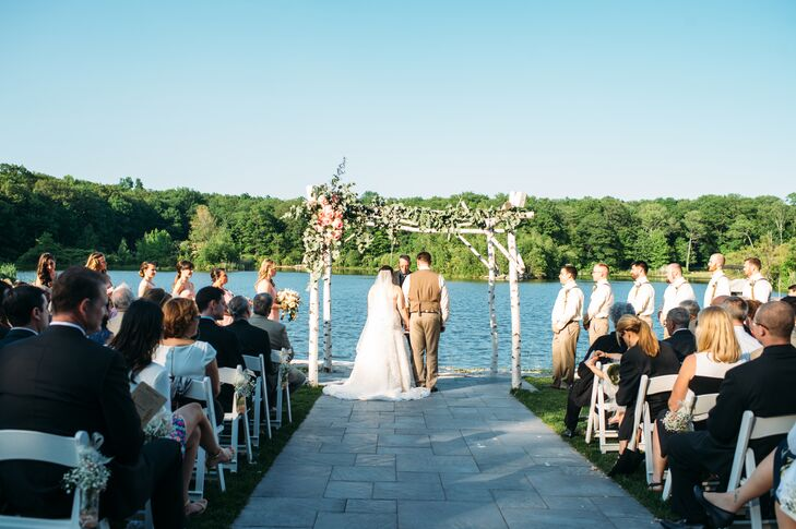 """Baby's breath marked every row of white folding chairs toward their romantic eucalyptus and rose-covered wedding arbor at Rock Island Lake Club in Sparta, New Jersey. As they stood below it, the couple took part in an ultra-personalized ceremony. """"The ceremony was done by a great family friend and second father practically, Glenn Craig,"""" Kim says. Their friends and family members also assisted in the service with two spoken Bible readings and poems."""