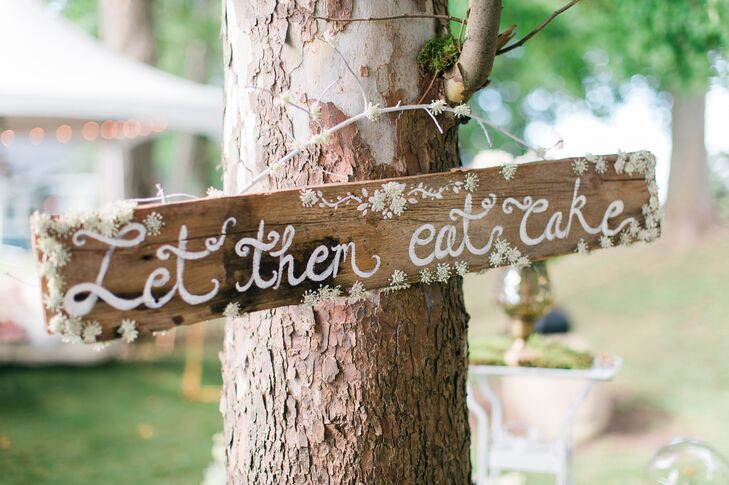 """As a nod to the Marie Antoinette-inspired motif, trees were hung with DIY wooden signs that read """"Let Them Eat Cake."""""""