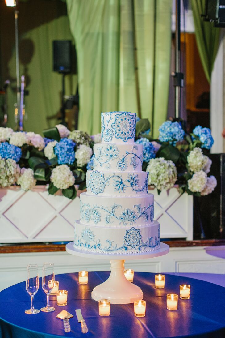 "The statement five-tiered wedding cake was decorated with a delicate blue floral pattern. ""We sent our baker the fabrics we were using as inspiration for the overall design,"" says Colleen."