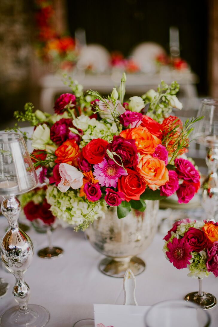 """""""We stuck with white and silver for the majority of the wedding because we wanted to make a statement with the flowers,"""" Marian says. """"We wanted to embrace the colors of San Miguel de Allende with the floral color palette."""" The couple brought their vision to life, decorating the tables with bountiful bouquets of roses, stock, hydrangeas and mums in brilliant shades of deep pink, red, burgundy and coral orange."""