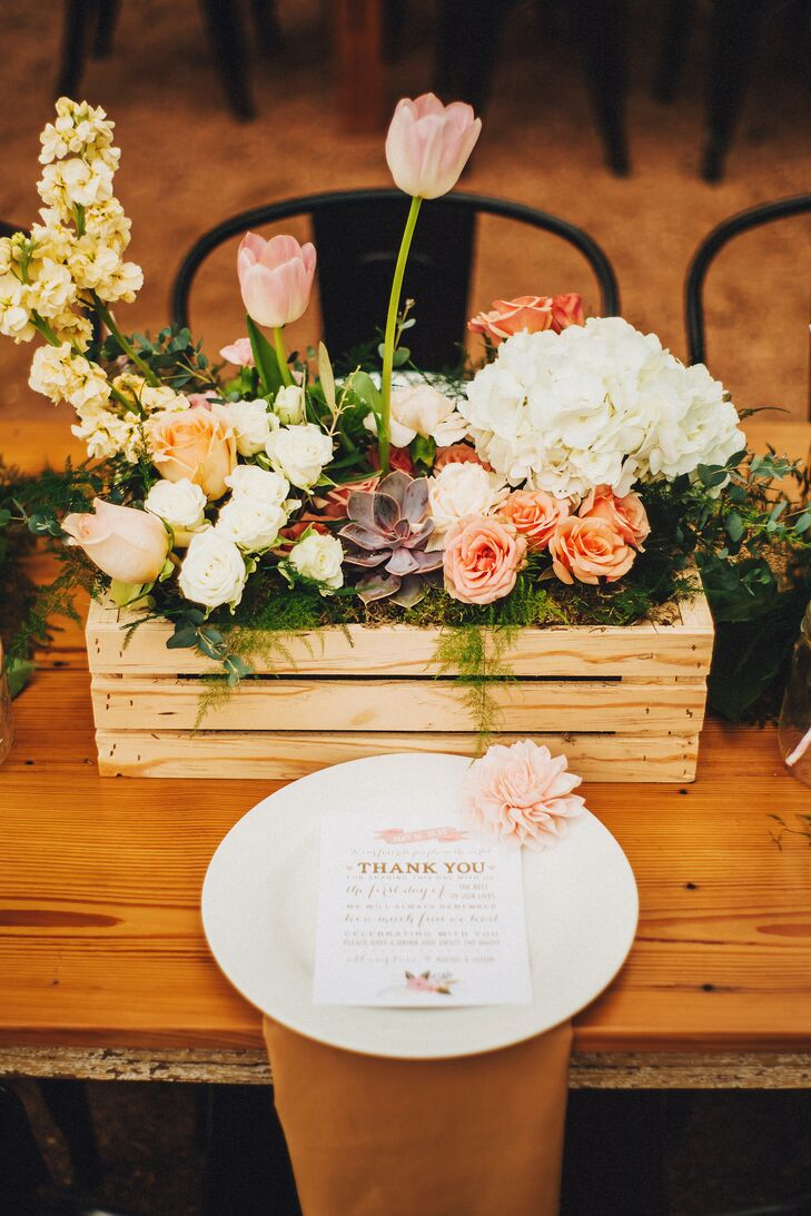 Every table at the reception had this chic centerpiece from the Flower Forrest. Pink tulips, peach and white roses, yellow delphiniums, succulents and white hydrangeas all pulled in the natural vibe in wooden breakaway vases. Different types of greenery, including eucalyptus and moss, filled out the arrangements and lined the finished wood tables.