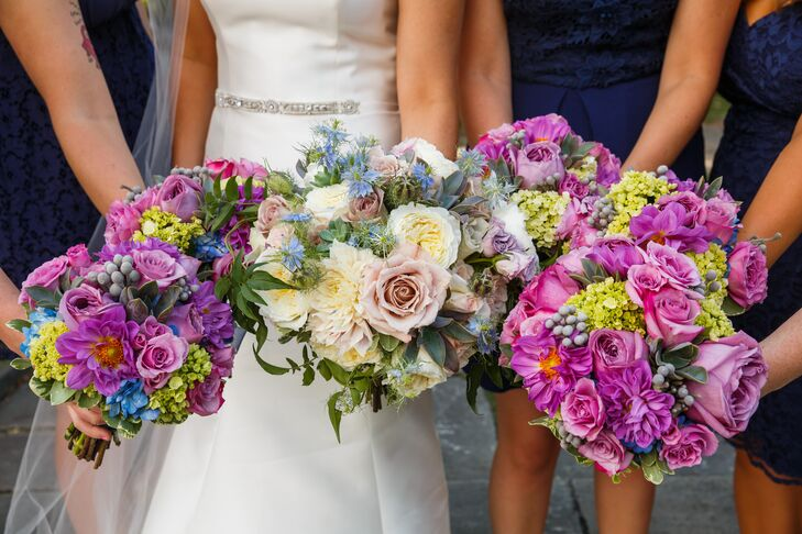 The bridesmaids bunched their bright purple round bouquets together, with Jackie's bouquet in the middle. The bridesmaid arrangements of roses, hydrangeas, silver brunia, ivy and jasmine made up the round shapes. The bridal bouquet embodied similar blooms but in shades of blush and champagne, all arranged by Plantscaping and Blooms.