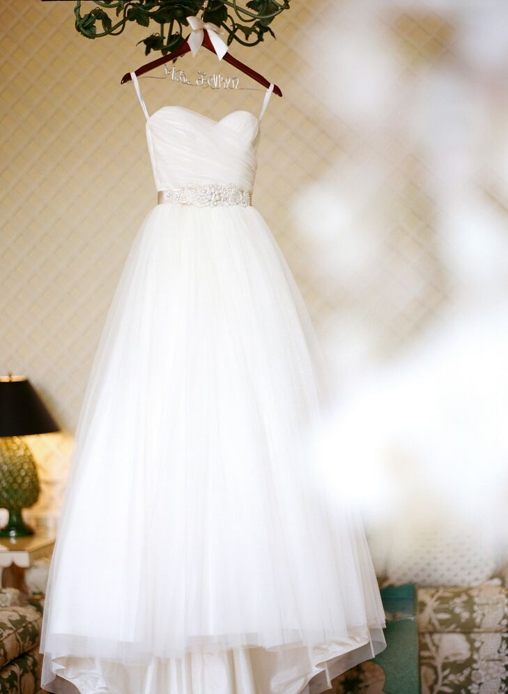 Katie wore a classic tulle A-line wedding dress with a belt by Erin Cole.