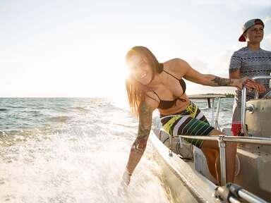 woman on boat splashing in ocean