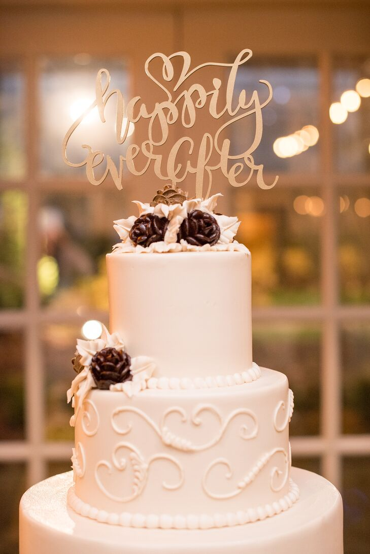 "The white buttercream-frosted cake featured alternating layers of cannoli and cookies and cream. The ""happily ever after"" cake topper played into the subtle fairy-tale theme, complemented by the deep wine floral accents."