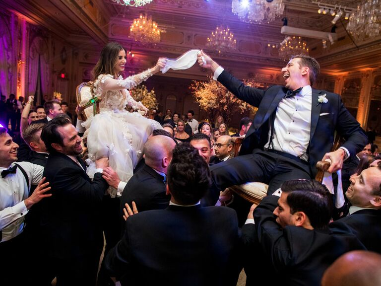 Bride and groom lifted in chairs by groomsmen during traditional Hora