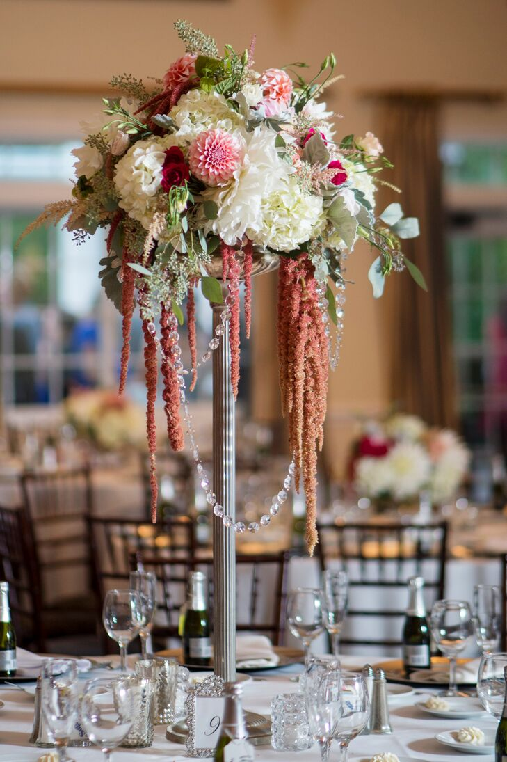 The couple worked with Stems Floral Design to create two centerpiece styles to infuse the Riverhouse's ballroom with texture and a romantic, laissez-faire flair. Alternating tables boasted lush bunches of ivory and blush hydrangeas surrounded by a halo of red amaranthus arranged high on silver stands and bright, low bundles of dahlias, hydrangeas and roses. Textured votive candles illuminated with soft, warm light introduced an air of inviting ambiance to each tabletop, while silver-framed table numbers offered a subtle note of old-world elegance.