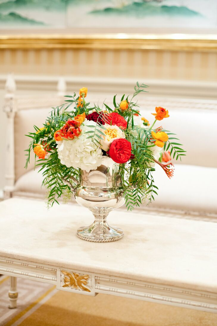 Hydrangeas, ferns and ranunculus filled antique-inspired silver vases in the lounge area.