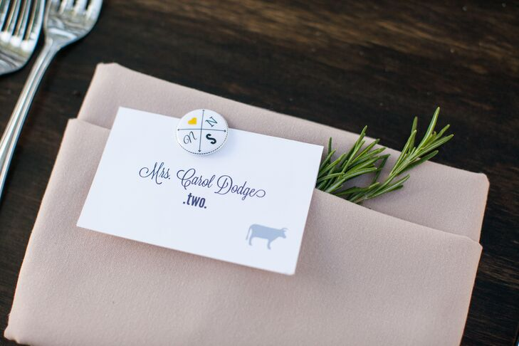 Escort cards were printed on white stationery and accented with dark blue text and animal designs. Each card was marked with a personalized pin that had the couple's logo on it, and were neatly positioned on top of beige napkins at the table for the wedding at Chateau Margene in Creston, California.