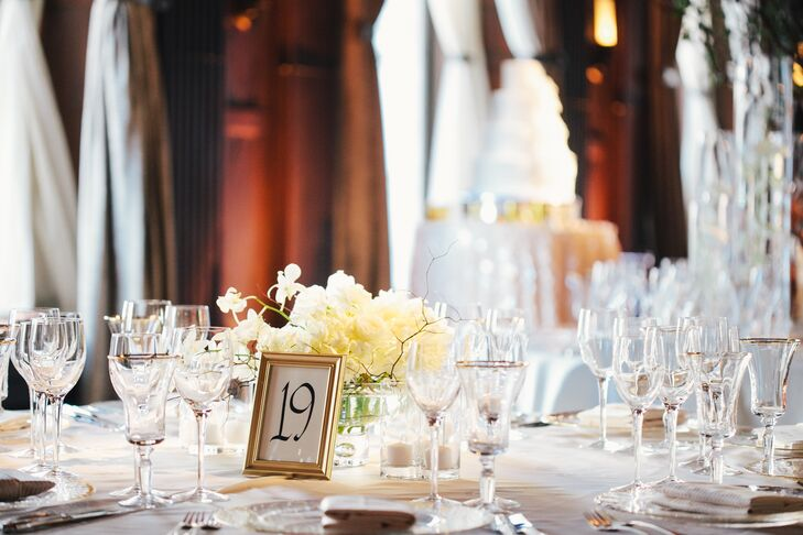 A gold framed table number was placed in front of an ivory hydrangea centerpiece on a dining table at the reception.