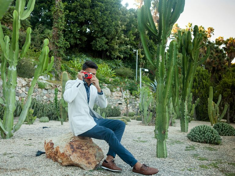 Man in white suit jacket with camera sitting in desert with cacti