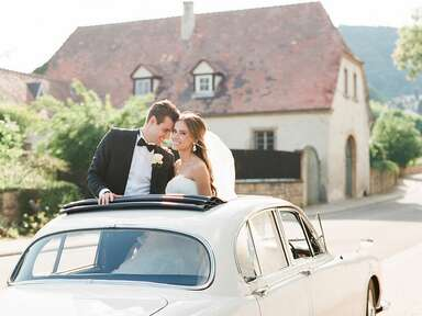 Groom and bride standing out of car sunroof in Germany