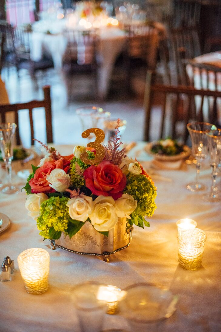 The gold glitter table numbers were placed in the coral and white rose centerpieces. Small candle votives surrounded the floral centerpieces at Thorpewood in Thurmont, Maryland.