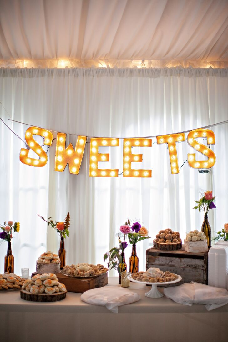 """Behind the dessert table, a """"Sweets"""" sign illuminated the space. The dessert table was also decorated with small rose flower arrangements in vintage-style bottles."""