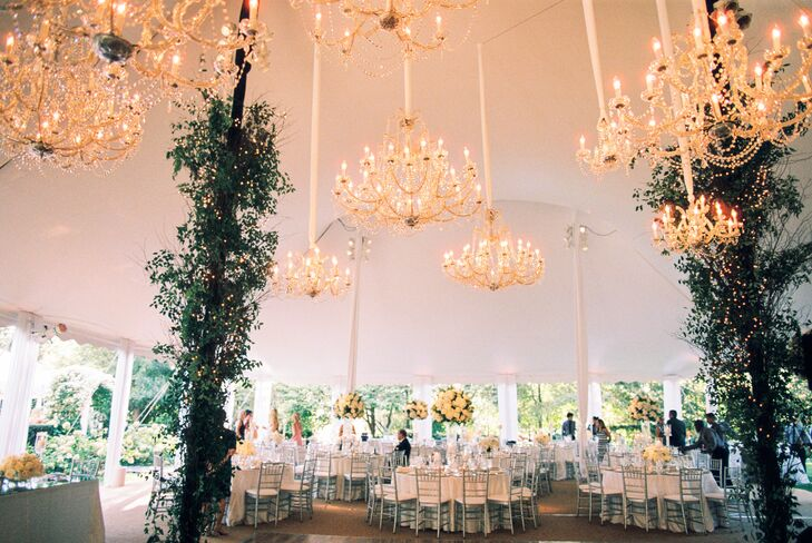 Crystal Chandeliers Illuminating White Tented Reception Space