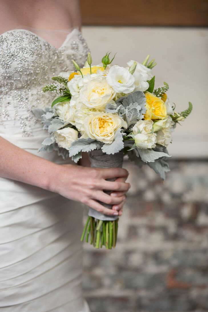 Emily held a ivory and yellow bouquet filled with an assortment of roses and accented with dusty miller.