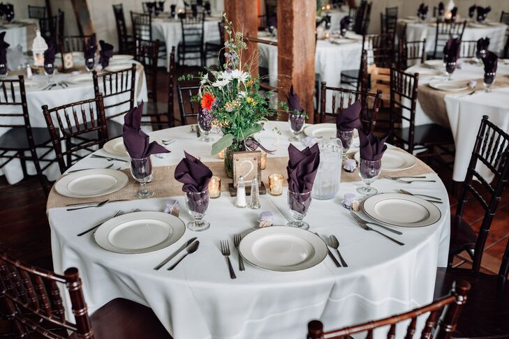 The reception tables were arranged with brown chiavari chairs and burlap table runners. The centerpieces, which were created by a family friend, consisted of wildflowers in mason jars, echoing the cocktail hour flower arrangements. The table numbers were written on burlap and displayed on wooden blocks.