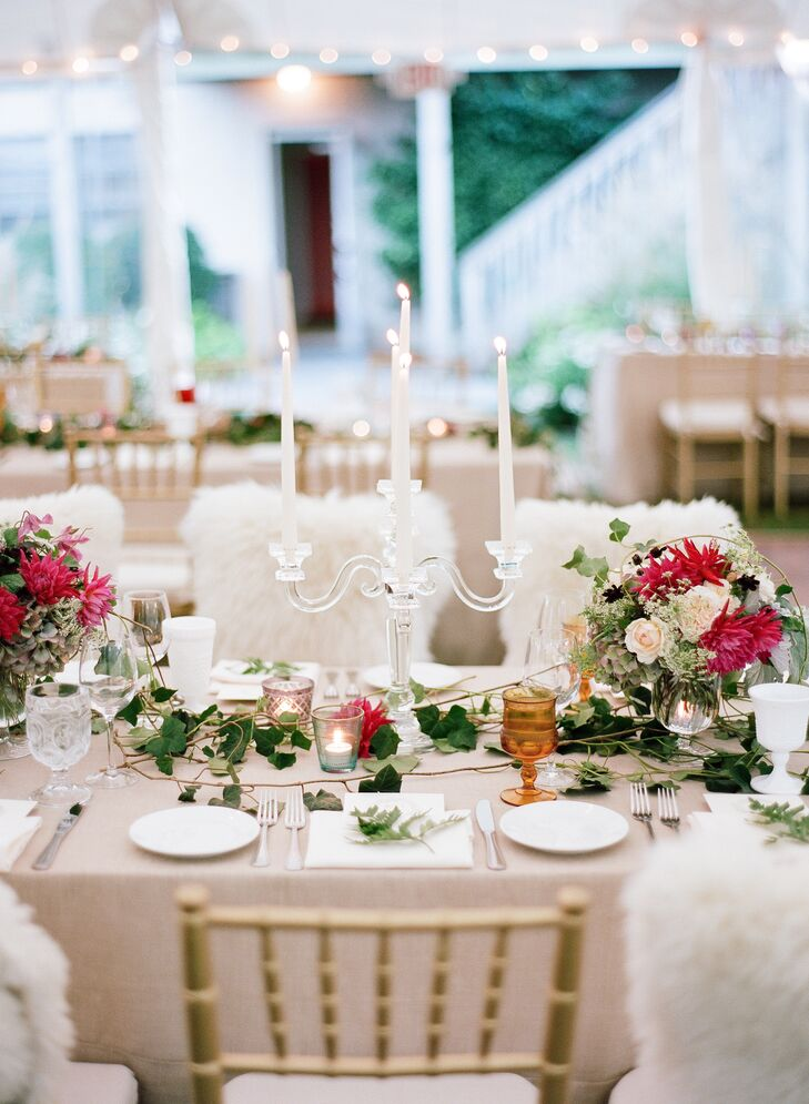In addition to a scattering of votive candles, the reception tables were illuminated by elegant crystal candelabras holding white tapered candles. The warm candlelight infused the room with romance and ambiance, tying in seamlessly with the garden-inspired centerpieces and cozy faux-fur throws.
