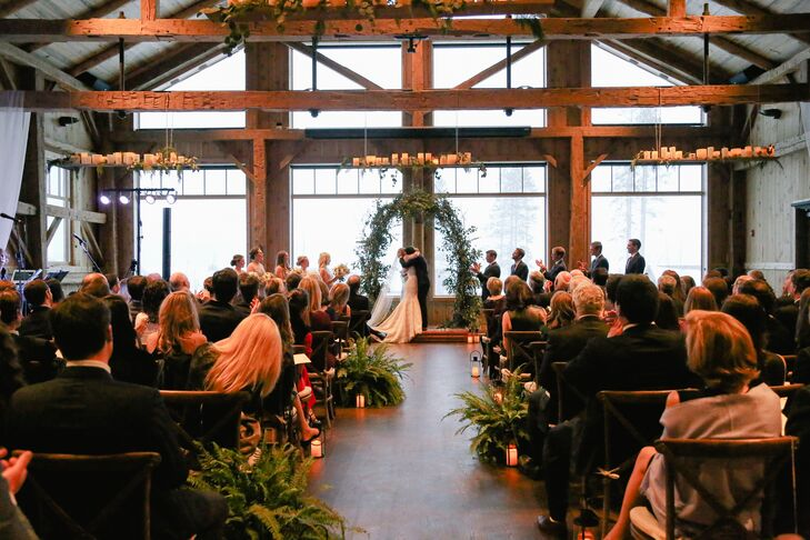 To add softness and romance to the rustic mountain barn at Devil's Thumb Ranch in Tabernash, Colorado, the aisle was lined with large unrestrained ferns and several candlelit lanterns in different sizes.