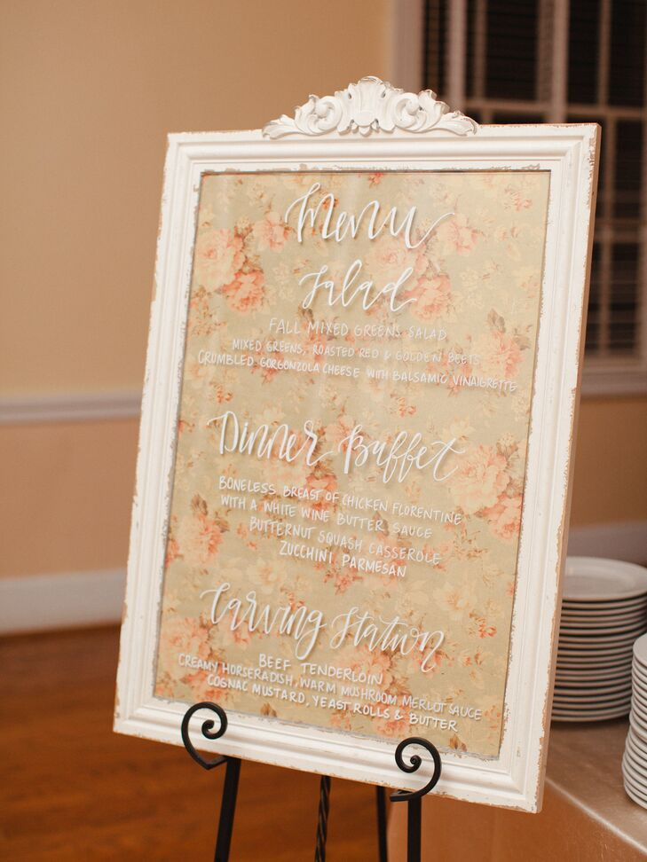 The couple displayed their dinner menu on a framed sign with white calligraphy and floral paper.